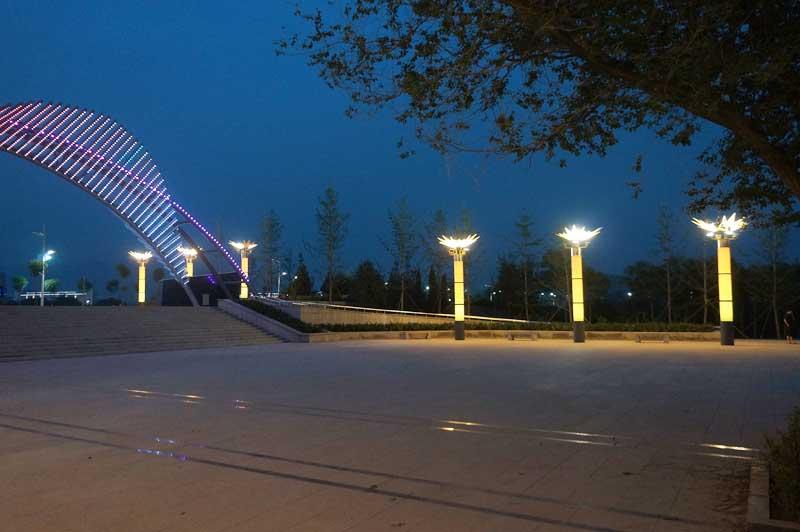 景区照明的意义在于通过对园区整体照明品质的提高,为将来景区周边的旅游开发、商业地产开发和人居环境树立形象、提升价值。 根据通州滨河森林公园周边城市规划发展方向,分析人流动向与各景区之间的关系,使照明设计定位更具有前瞻性和可持续性。 本次灯光照明设计北起东六环路潞阳桥至干棠大桥之间的区域 ,主要包含潞河桃柳景区、月岛闻莺景区、丛林活力景区、银枫秋实景区、明镜移舟景区共五个景区、十五个景点。灯光设计主题为:光耀变迁•宁静致远。照明设计定位为:唤醒沉睡中的运河,打造舒适宜人的休闲环境。 公园主入口广